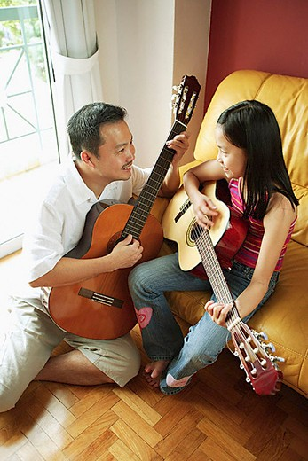 Father and daughter holding guitars, sitting face to face : Stock Photo