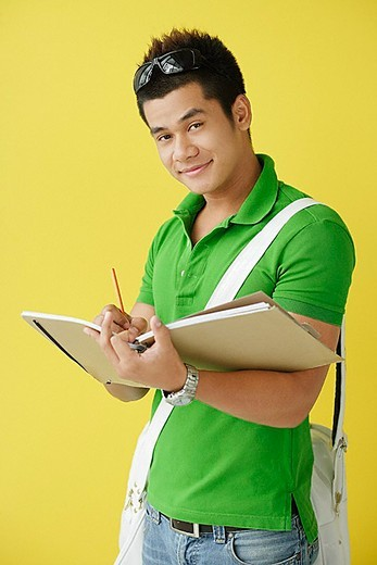 Man standing against yellow background, writing in notebook, looking at camera : Stock Photo