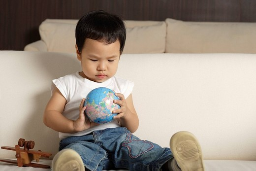 Baby boy playing with globe : Stock Photo