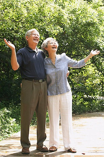 Senior couple looking up, hands outstretched : Stock Photo