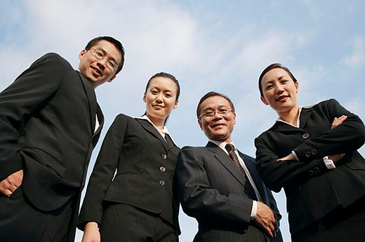 Businessmen and businesswomen looking down at camera : Stock Photo