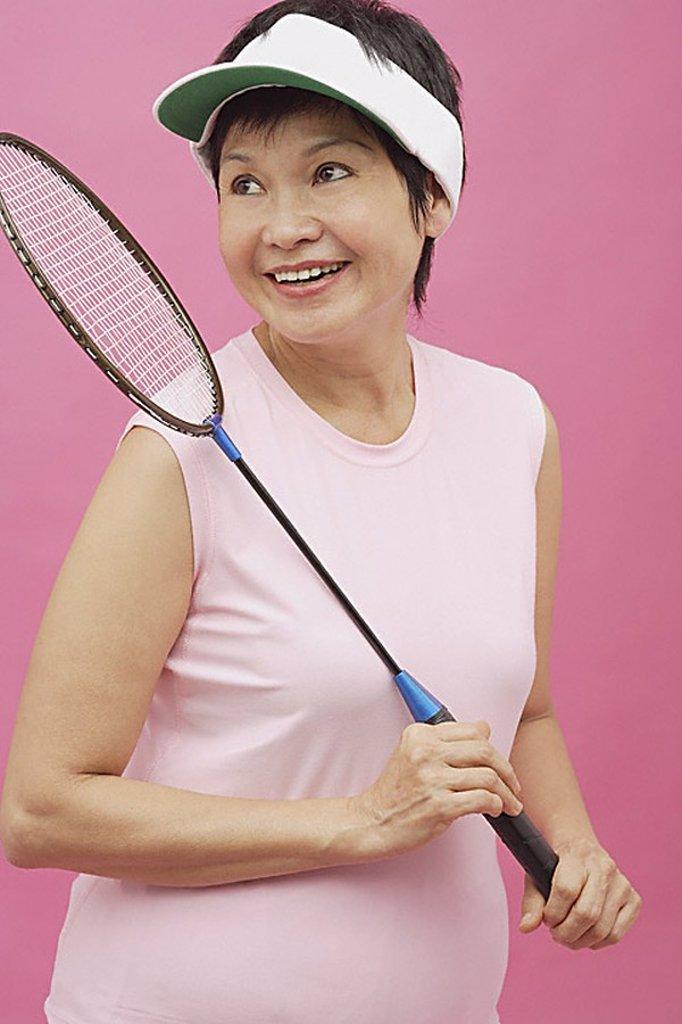Stock Photo: 4079R-9156 Mature woman holding badminton racket