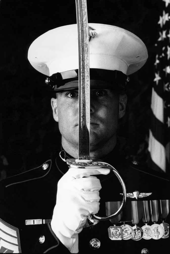 Stock Photo: 4080-139 Marine officer holding a sword in front of his face