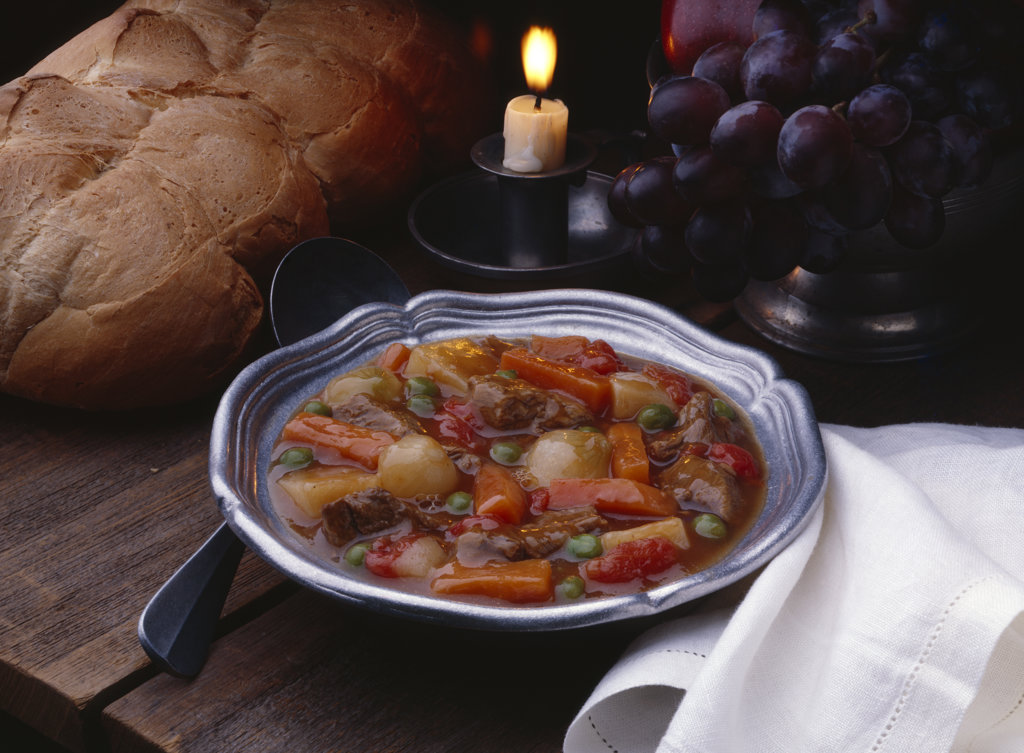 Close-up of a beef stew on a bowl with red grapes : Stock Photo