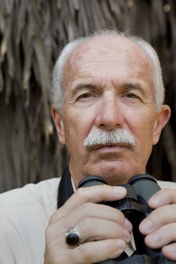 Stock Photo: 4084R-1328 Balding Eldery Man With Moustache Holding Binoculars