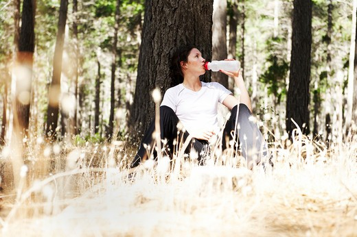 Stock Photo: 4085-138A Young woman drinking water after jogging in a forest