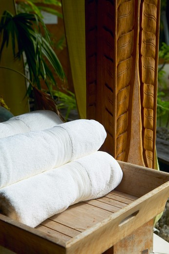 Close-up of rolled up white towels on a tray at a spa : Stock Photo