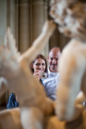 Couple taking picture of a statue in a museum : Stock Photo