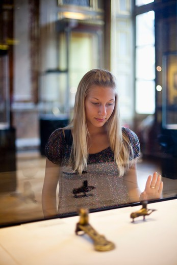 Teenage girl watching Egyptian relics in a museum, Paris, Ile-de-France, France : Stock Photo