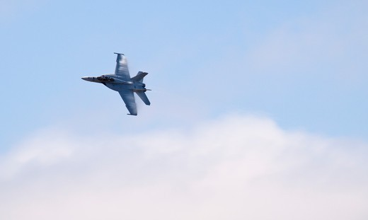 A Boeing F-18 Super Hornet performing a high speed pass at the Watsonville, CA airshow. The Boeing F/A-18F Super Hornet is a carrier-based strike fighter aircraft. The Super Hornet has an internal 20 mm gun and can carry various air-to-air missiles and air-to-surface weapons.   Designed and initially produced by McDonnell Douglas, the Super Hornet first flew in 1995. : Stock Photo