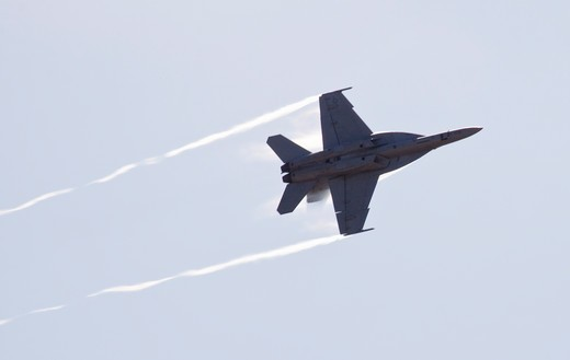 Stock Photo: 4093-10030 A Boeing F-18 Super Hornet performing a high speed pass at the Watsonville, CA airshow. The Boeing F/A-18F Super Hornet is a carrier-based strike fighter aircraft. The Super Hornet has an internal 20 mm gun and can carry various air-to-air missiles and air-to-surface weapons.   Designed and initially produced by McDonnell Douglas, the Super Hornet first flew in 1995.