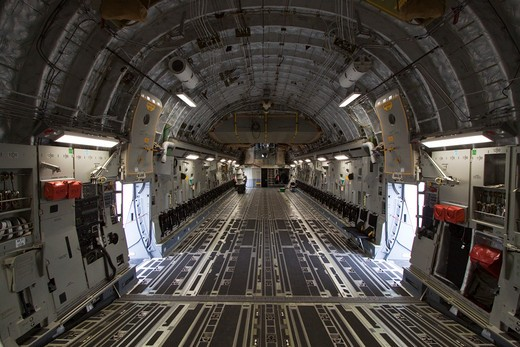 Interior view of the cargo area of a Boeing C-17 (formerly McDonnell Douglas). The C-17 Globemaster III is a large military transport aircraft. It was developed for the United States Air Force and is used for rapid strategic airlift of troops and cargo to main operating bases or forward operating base anywhere in the world. It has the ability to rapidly deploy a combat unit to a potential battle area and sustain it with on-going supplies. : Stock Photo