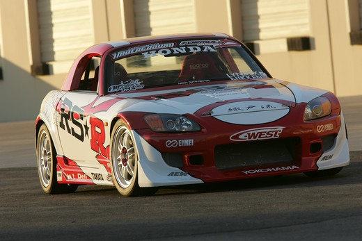 Stock Photo: 4093-10764 2004 Honda s2000 s-2000 Hardtop racing version race type   S2000 features a front-mid-engine, rear wheel drive layout with power being delivered via a Torsen limited slip differential mated to a six-speed manual transmission.  The S2000 comes with an electrically powered cloth top, and an OEM hardtop is also available.  The 2004 model introduced newly designed 17 wheels and Bridgestone RE-050 tires along with a retuned suspension that reduced the car's tendency to oversteer. The spring rates and