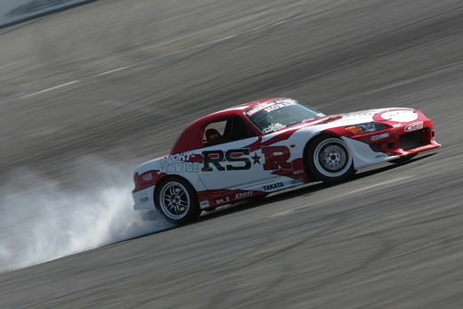 Stock Photo: 4093-10765 2004 Honda s2000 s-2000 Hardtop racing version race type burning rubber on the race track white smoke    S2000 features a front-mid-engine, rear wheel drive layout with power being delivered via a Torsen limited slip differential mated to a six-speed manual transmission.  The S2000 comes with an electrically powered cloth top, and an OEM hardtop is also available.  The 2004 model introduced newly designed 17 wheels and Bridgestone RE-050 tires along with a retuned suspension that reduced the car