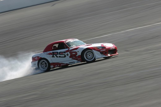 2004 Honda s2000 s-2000 Hardtop racing version race type burning rubber on the race track white smoke    S2000 features a front-mid-engine, rear wheel drive layout with power being delivered via a Torsen limited slip differential mated to a six-speed manual transmission.  The S2000 comes with an electrically powered cloth top, and an OEM hardtop is also available.  The 2004 model introduced newly designed 17 wheels and Bridgestone RE-050 tires along with a retuned suspension that reduced the car : Stock Photo