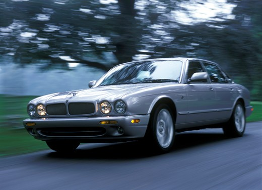 Jaguar XJR 2000 silver trees street : Stock Photo