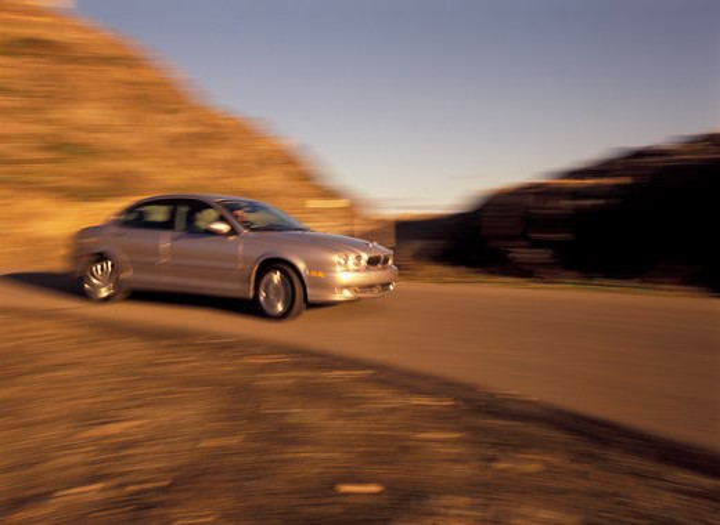 Jaguar X-Type 2002 silver curve cornering street : Stock Photo