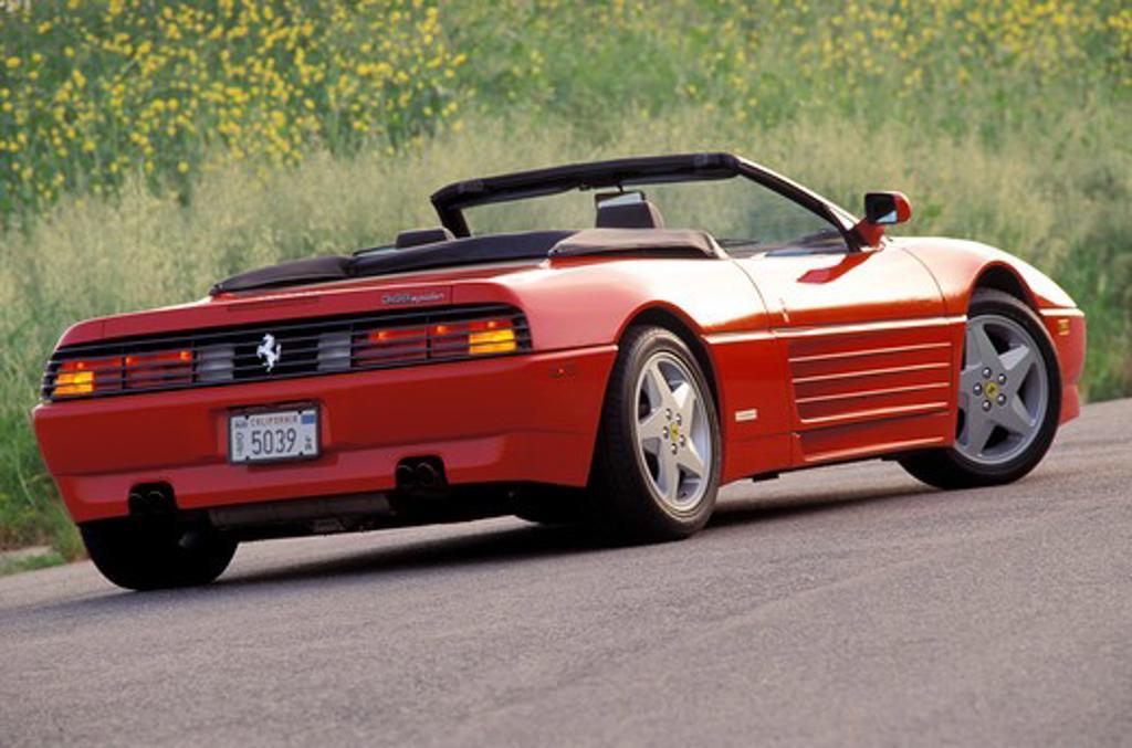 Stock Photo: 4093-11898 Ferrari 1993 348 Spider red rear 3/4 beauty asphalt brush wildflowers 1990s street