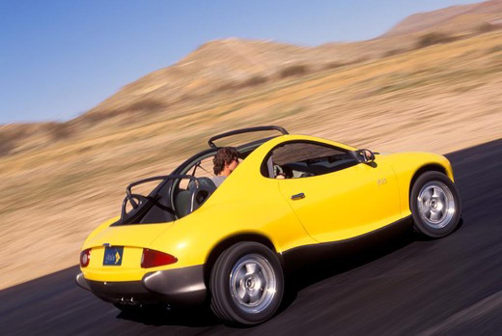 Stock Photo: 4093-11933 Hyundai HCDIII concept show car prototype yellow rear 3/4 asphalt pavement man street