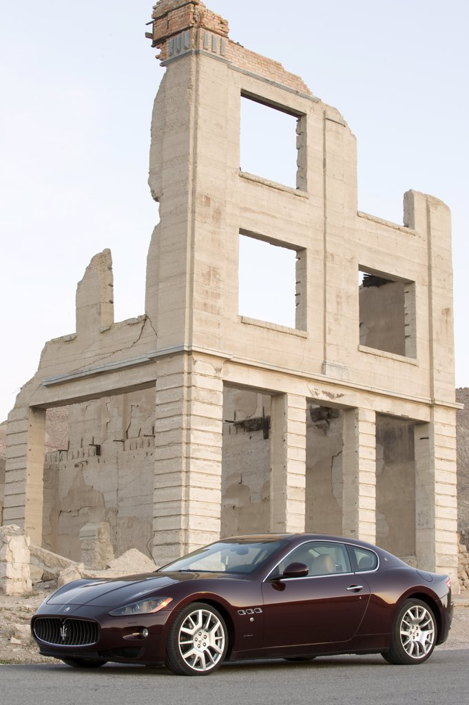 Maserati GranTurismo parked by dilapidated building : Stock Photo