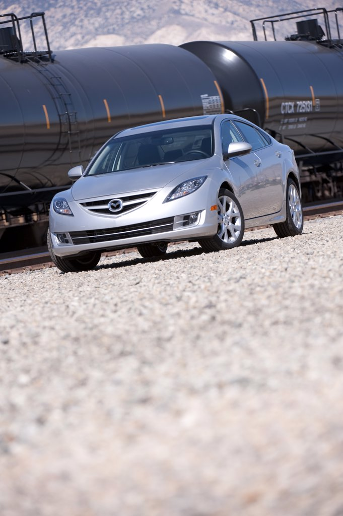 Silver Mazda 6 parked by goods train, side view : Stock Photo