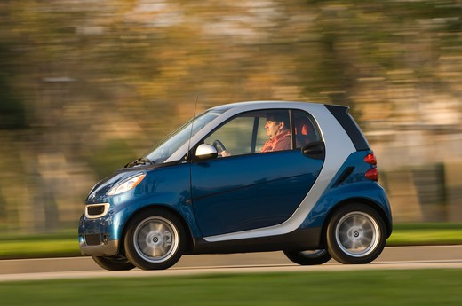 Smart ForTwo Passion Cabriolet driving along road, side view : Stock Photo