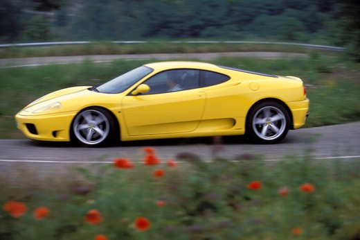 Stock Photo: 4093-15530 Ferrari 1999 360 Modena yellow profile asphalt wildflowers brush 1990s street