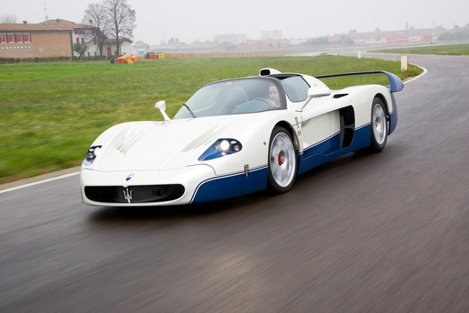 Front 3/4 action view of a 2007 Maserati MC 12. The Maserati MC12 is a grand tourer produced by Maserati to allow a racing variant to compete in the FIA GT Championship. Maserati designed and built the car on the chassis of the Enzo Ferrari. : Stock Photo
