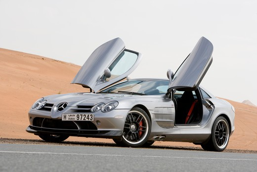 A front 3/4 view of the 2007 Mercedes-Benz McLaren SLR 722 with the unusual gull-wing doors open. The 722 refers to the victory by Stirling Moss and his co-driver Denis Jenkinson in a Mercedes-Benz 300 SLR with the starting number 722 (indicating a start time of 7:22 a.m.) at the Mille Miglia in 1955. The 722 Edition creates 650 bhp, with a top speed of 337 km/h (5 more than the standard SLR). A new suspension is used with 19-inch light-alloy wheels, a stiffer damper configuration and 0.4 inches : Stock Photo