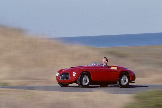 Stock Photo: 4093-16795 1951 Ferrari 166 MM Barchetta action front 3/4 Lusso touring race car. The 166 MM Touring Barchetta, a Ferrari masterpiece, still increase pulse rates fifty-five years later. It is the first Ferrari sports car; all previous cars were strictly for racing. Craftsmen welded a tubular frame with a 2,200 mm wheelbase to hand-formed body panels. Beneath the hood resides a Colombo designed 1,995 cc 60-degree V-12. The 166 MM was arguably the world's fastest sports car in its day. In the heyday, it reco