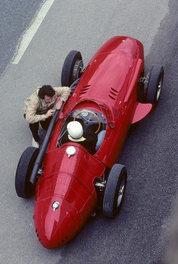 Stock Photo: 4093-16835 1957 Maserati 250F race car beauty static overhead people. The Maserati 250F (first raced January 1954 - last raced November 1960) was a racing car made by Maserati of Italy, used in '2.5 litre' Formula One racing (thus, the '250' and 'F'). 26 examples were made in total. It was introduced for the 1954 Formula One season and remained in use by customer teams until 1960.  The Maserati is on the old Reims race track. Between 1925 and 1969, Reims hosted the Grand Prix de la Marne automobile race