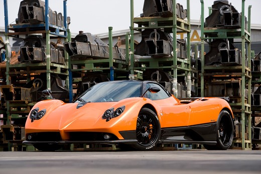 Stock Photo: 4093-17096 2005 Zonda F has a 7.3 L V12 a very fast 3.5 second sprint to 62 mph. Bright orange outdoors in a junkyard or industrial area
