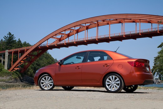 Stock Photo: 4093-17190 Rear 3/4 view of a 2010 red Kia Forte in front of an arch bridge