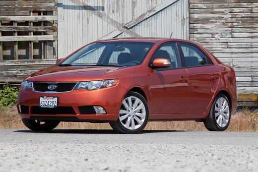 Front 3/4 static view of a 2010 red Kia Forte on a rural road in front of an old barn : Stock Photo