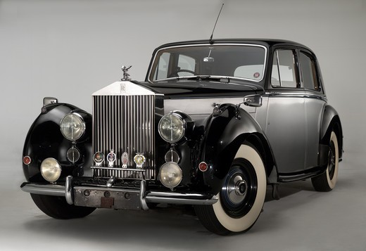 Front 3/4 view of a black and silver 1949 Rolls Royce Silver Dawn photographed on a white background. : Stock Photo
