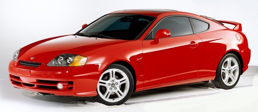 Front 3/4 view of a red Hyundai Tiburon photographed in the studio with a white background. : Stock Photo
