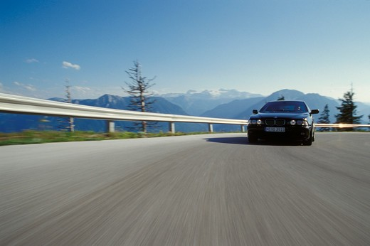 BMW 5 Series 2000 black cornering curve guard rail street : Stock Photo