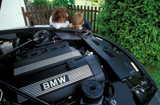 Stock Photo: 4093-17978 detail BMW engine children kids boy girl fence city