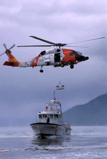 Sikorsky Military Helicopters Aviat USCG U.S. Coast Guard motor lifeboat boat 47-foot self-righting Textron Marine Systems HH-60J Jayhawk airlift : Stock Photo
