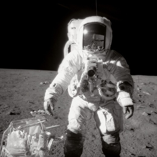 Astronaut Alan L. Bean  Lunar Module pilot  pauses near a tool carrier during extravehicular activity (EVA) on the Moon's surface. Commander Charles Conrad Jr.  who took the black and white photo  is reflected in Bean's helmet visor. : Stock Photo