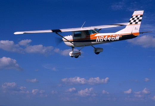 Stock Photo: 4093-21262 1970's Cessna C150 C 150 Aerobat. Built from 1970 to 1977. This variant of the Cessna 150 trainer is structurally enhanced for limited +6/-3g aerobatics. The Aerobat features skylights  four point harnesses  G-meter  quick jettison doors  and removable seat cushions so parachutes can be worn. This particular plane is flying over a midwestern town.