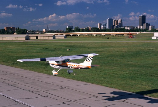 Stock Photo: 4093-21264 1970's Cessna C150 C 150 Aerobat. Built from 1970 to 1977. This variant of the Cessna 150 trainer is structurally enhanced for limited +6/-3g aerobatics. The Aerobat features skylights  four point harnesses  G-meter  quick jettison doors  and removable seat cushions so parachutes can be worn. This particular plane is landing at a small airport.