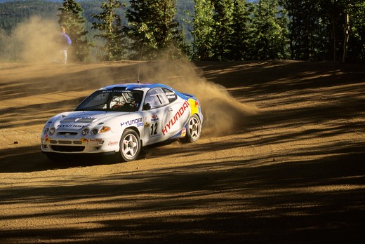 Stock Photo: 4093-21945 Hyundai Tiburon white cornering sliding drifting dust dusty shadows Pikes Peak Hill Climb