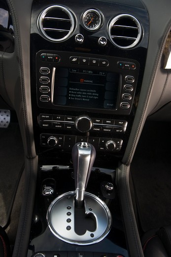 Interior detail view of a 2009 Bentley Continental GT showing the shifter, radio and GPS navigation display. : Stock Photo