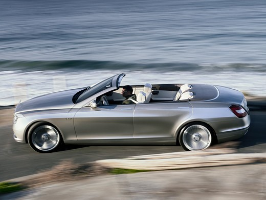 The Mercedes-Benz Ocean Drive is a concept car introduced in 2007. The car is built on the S600 sedan chassis. It's a four door convertible with a soft top. It's not known whether the car will be produced. Profile panning action view of the car on a rural road at the beach. : Stock Photo
