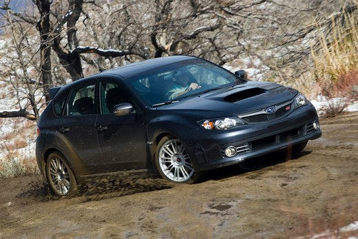 Front 3/4 action view of a 2009 Subaru Impreza WRX STi on a muddy, rural road kicking up mud. : Stock Photo