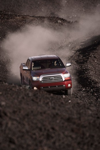 Stock Photo: 4093-22775 Front action view of a 2009 Toyota Tundra on a dirt road.
