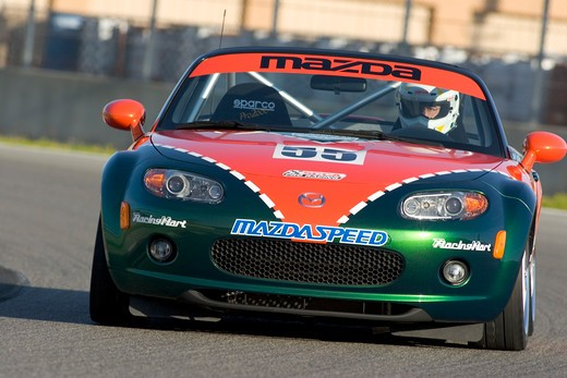 Mazda Miata MX-5 2006 Laguna Seca orange green turning cornering handling : Stock Photo