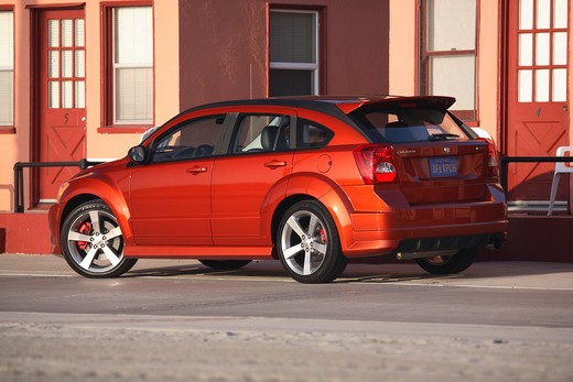 Stock Photo: 4093-23831 2008 Dodge Caliber SRT4 parked in front of a row of houses on an empty road.