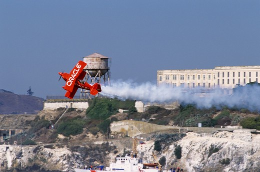 Air show performer Sean Tucker in the Oracle Challenger trails smoke as he flies in front of Alcatraz Island during San Francisco's Fleetweek air show. : Stock Photo